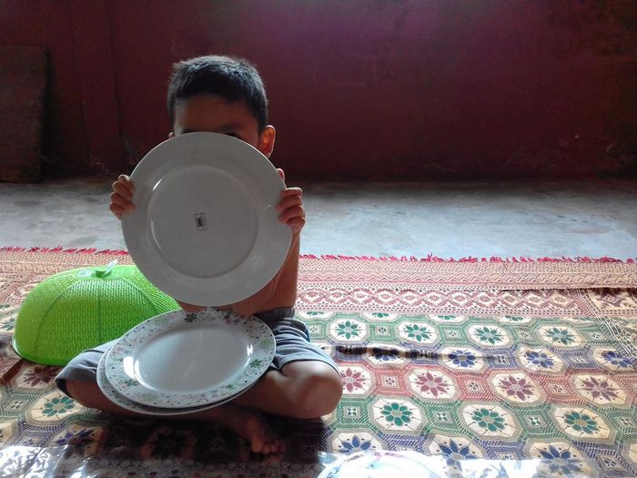A boy is playing with the dishes. Dishes Boy Home Carpet - Decor 10 The Creative - 2018 EyeEm Awards