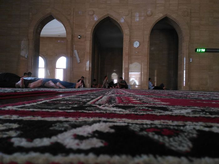 People Relaxing On Rug At Mosque
