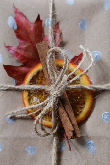Close-up of cinnamon and citrus fruit tied with threads on paper