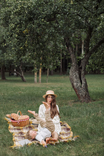 Woman sitting in basket on grass against trees