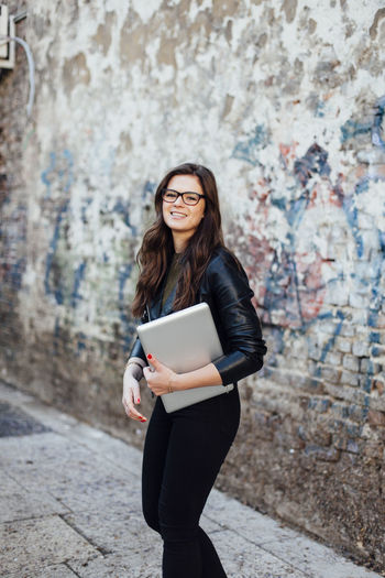 Young woman holding laptop outdoors