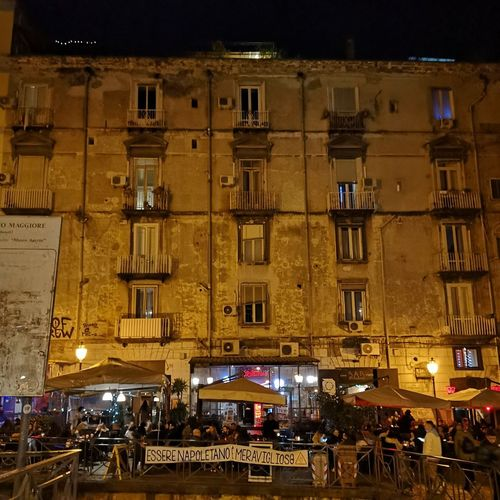 People on illuminated street against buildings in city at night