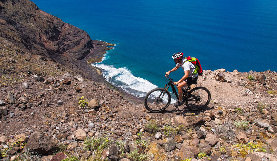 Man riding bicycle by cliff against sea