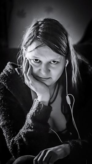 Portrait of woman with hand on chin listening music