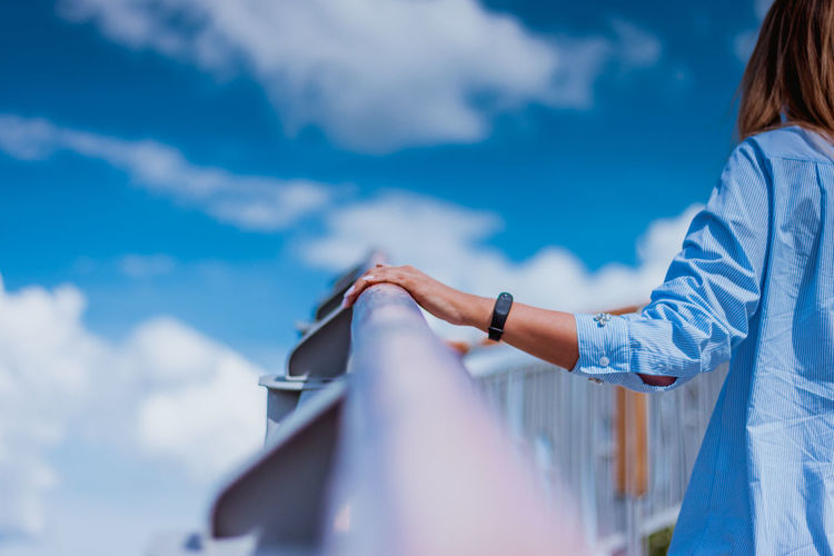 Midsection of woman standing by railing against sky