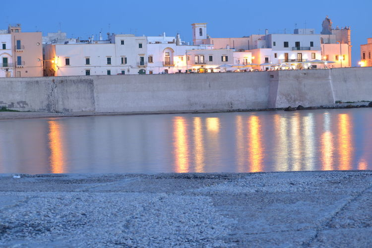 Canal By Illuminated Buildings In Puglia At Dusk