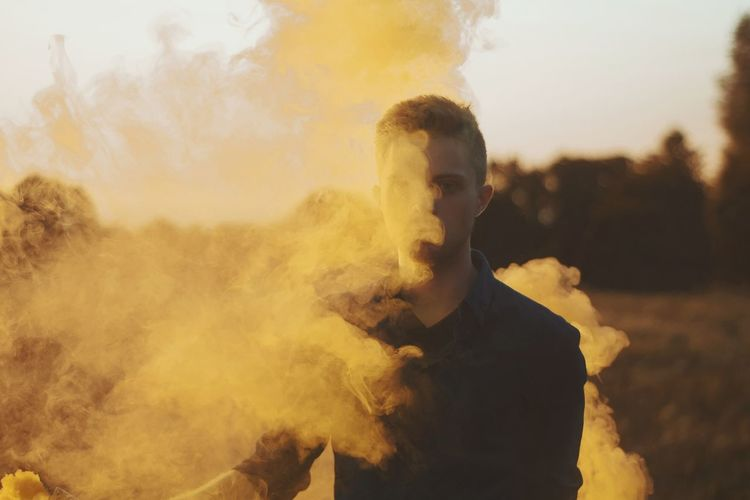 Portrait of young man standing amidst smoke outdoors