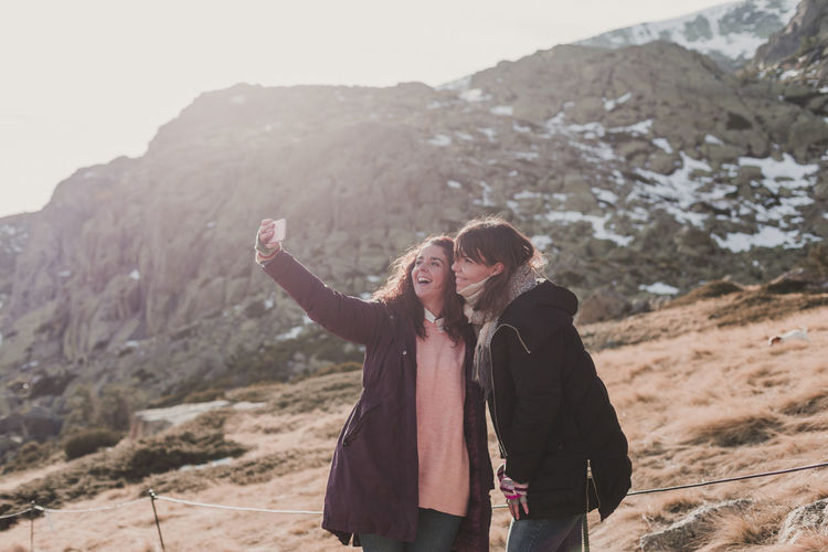 Women taking selfie while standing on mountain against sky