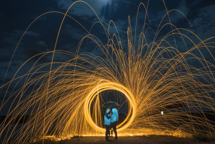 Couple holding umbrella while illuminated wire wool at night