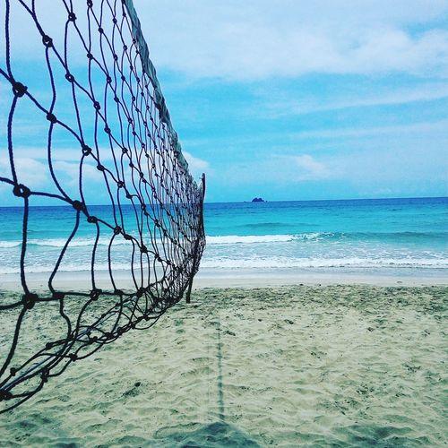 Volleyball net on beach against cloudy sky