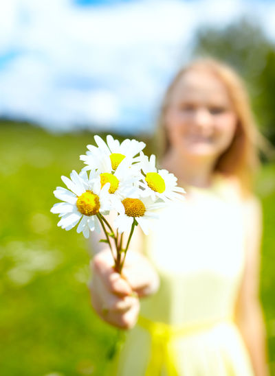 Close-up of woman holding white flowers on sunny day