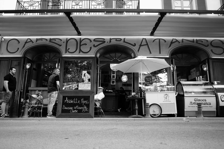 Café des Platanes Adult Architecture Bar Building Exterior Built Structure Cafe City Day Food And Drink Group Group Of People Lifestyles Men Outdoors People Real People Small Business Street Street Photography Streetphotography Text Women