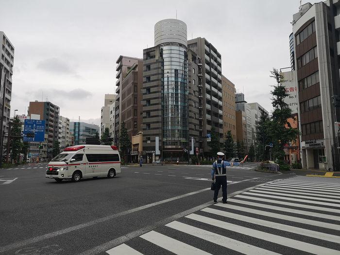 Vehicles crossing road against buildings in city