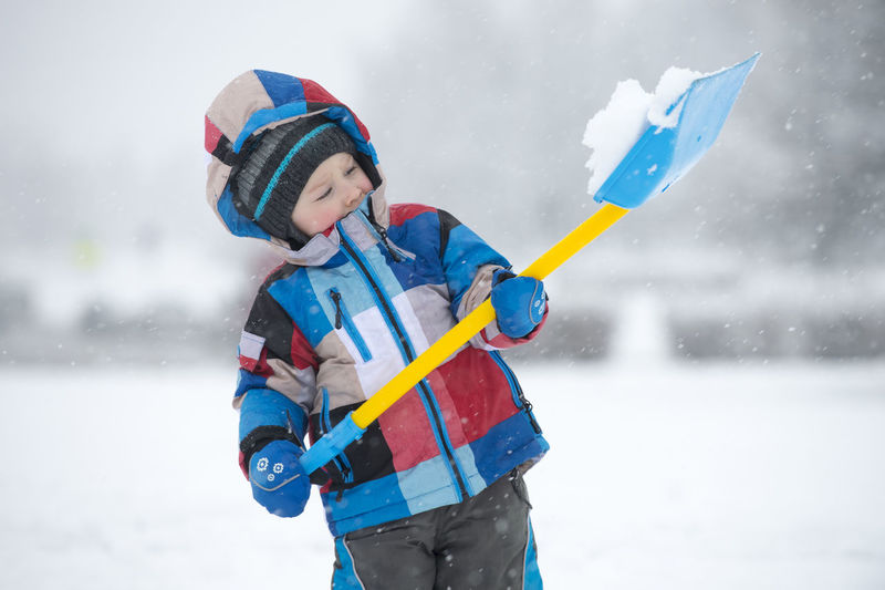 Cute boy holding snow in shovel on field during winter