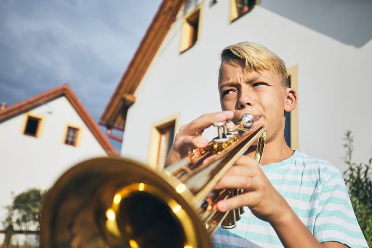 Little boy playing the trumpet in front of the house. Children Creativity Learning Skill  Sound Boys Candid Child Childhood Enjoyment House Males  Music Musical Instrument Musician Outdoors Passion Playing Portrait Practicing Pre-adolescent Child Real People Rural Scene Talent Trumpet