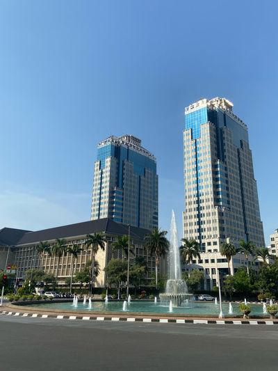 Fountain against modern buildings in city against clear blue sky