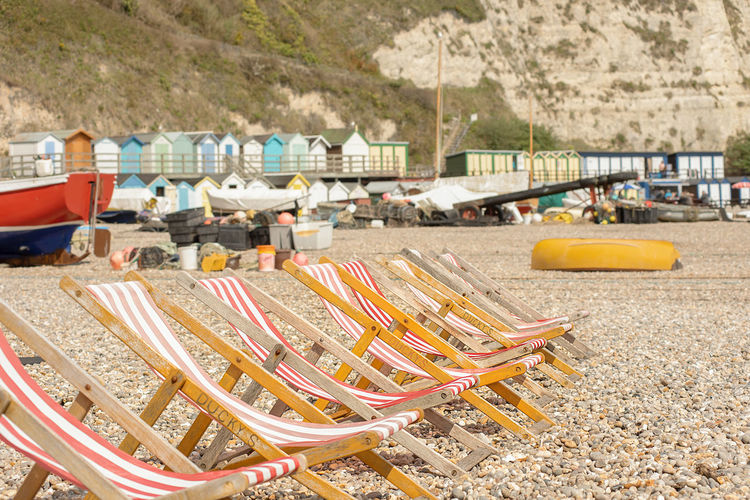 A row of empty traditional wooden frame deck chairs with red and white striped material on a pebble beach with beach huts and chalk cliffs in the background. Beer, Devon, UK. Relaxing Architecture Beach Beach Chairs Built Structure Day Deck Chairs Focus On Foreground Land Multi Colored Nature No People Outdoors Plastic Sunlight Travel Travel Destinations Water