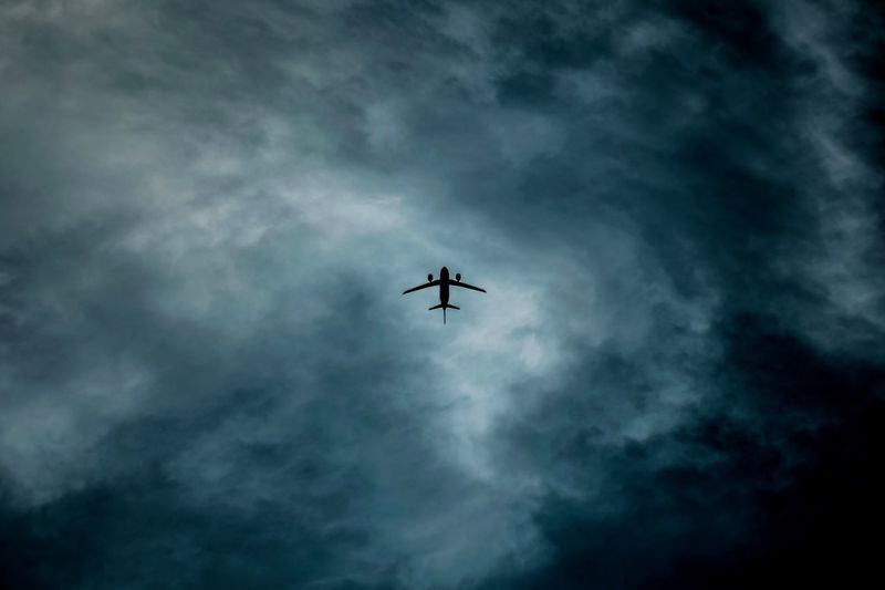 Low angle view of airplane flying against storm cloud