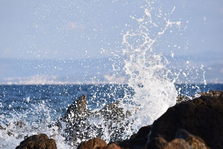 Wave splashing on rocks in sea against sky