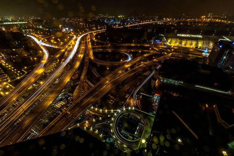 High angle view of illuminated multiple lane highway in city at night during monsoon