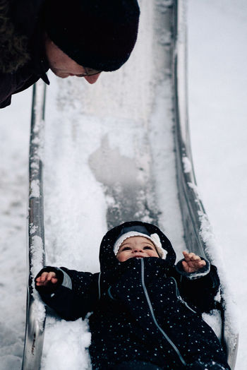 Father looking at baby girl playing on snow covered slide