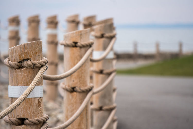 Grass Leading Lines Beach Close Up Close-up Day Fence Focus On Foreground Horizon Lake Lakeshore Nature No People Outdoors Pattern Pavement Posts Rope Shore Sky Tied Up Waterfront Wooden