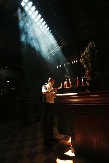 Full length of man burning candle while standing in temple