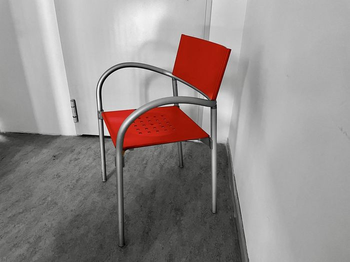 Close-up of empty chair against wall