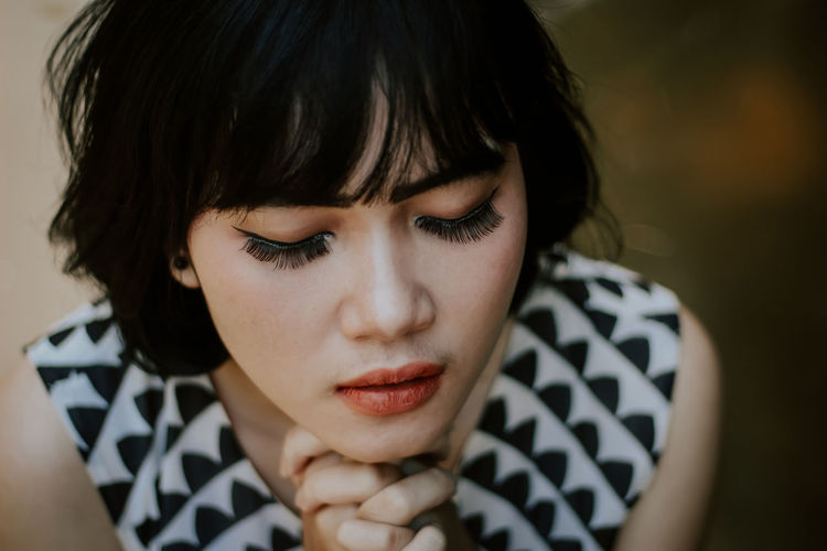 High angle close-up of young woman praying
