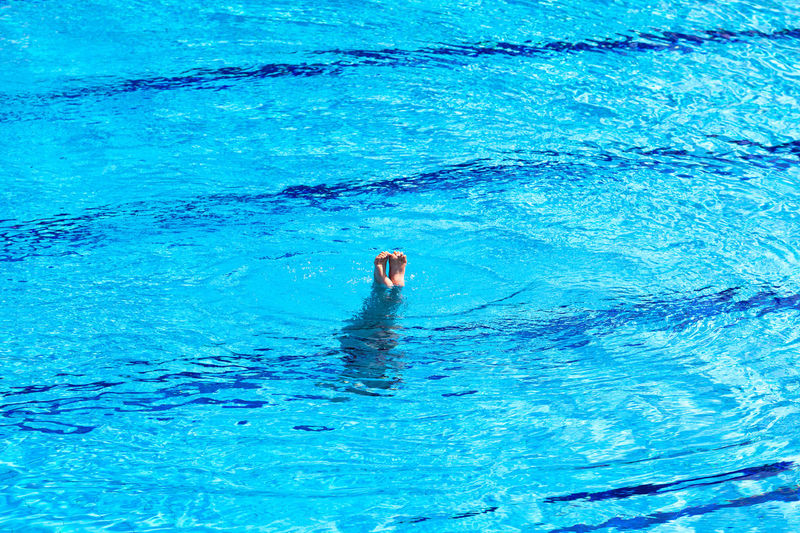 Woman doing handstand in the clear blue swimming pool water, feet in the air above the water surface Swimming Water Blue Lifestyles Leisure Activity Motion Sport Swimming Pool Swimmer Diver Feet Legs Leg Foot Diving Dive Sports Water Sport Clear Blue Water Active barefoot