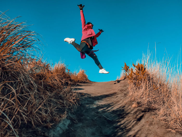 Low angle view of man jumping on plant against sky