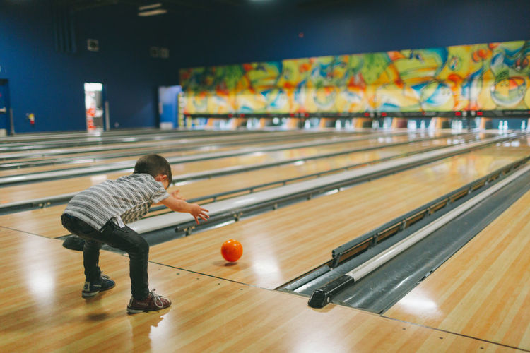 A little boy bowling at the bowling alley. Sport Leisure Activity One Person Full Length Ball Lifestyles Playing Indoors  Childhood Bowling Bowling Alley Throwing  Boy Child