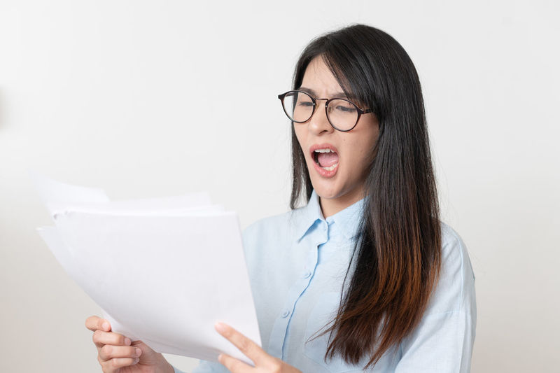 Portrait of beautiful woman holding paper against white wall