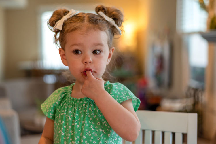 Cute girl eating chocolate at home