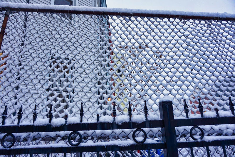 Chainlink fence in snow covered field seen through railing