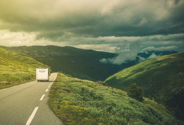 Motor Home Moving On Road Amidst Mountains Against Sky