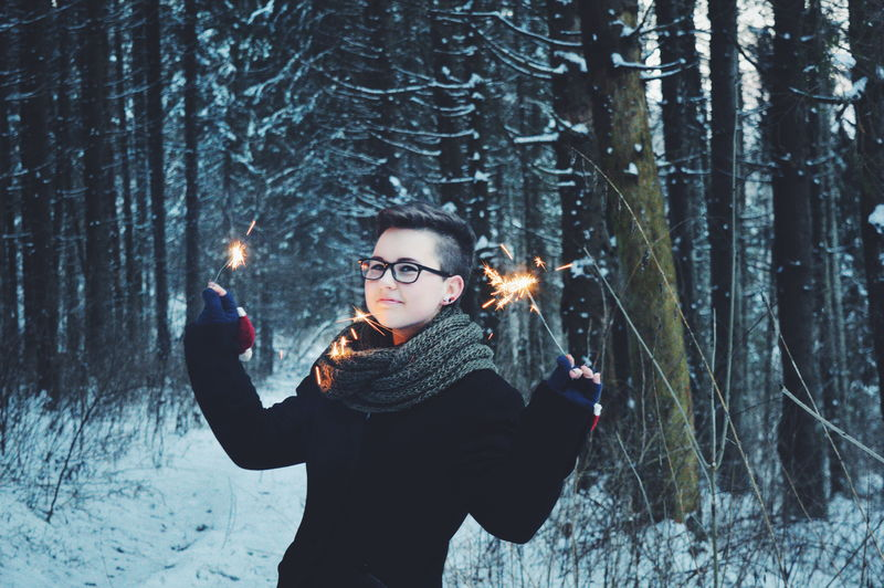 Portrait of young woman holding lit sparklers in forest
