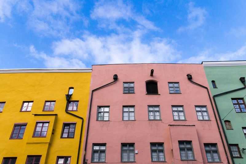 Building Exterior Architecture Sky Built Structure Low Angle View Cloud - Sky Window Building Residential District No People Day Nature City Blue Outdoors Yellow Multi Colored In A Row Sunlight Orange Color Apartment