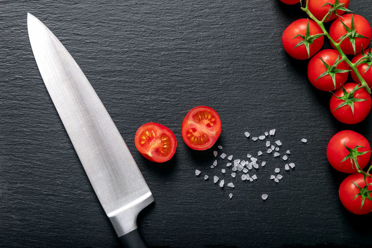 Background with fresh tomatoes on the vine and a cutting knife on black slate stone background Food And Drink Red Freshness Vegetable Food Tomato High Angle View Wellbeing Directly Above Still Life Slate - Rock Ingredient Close-up Vegetarian Food Healthy Eating Fruit Table Knife Vine Salt Tomato Sauce Backgrounds Kitchen Cooking Cut