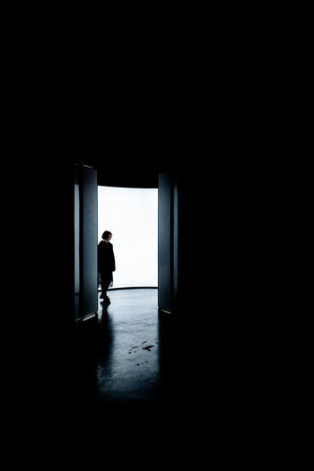 Silhouette of a woman standing at the entrance of building