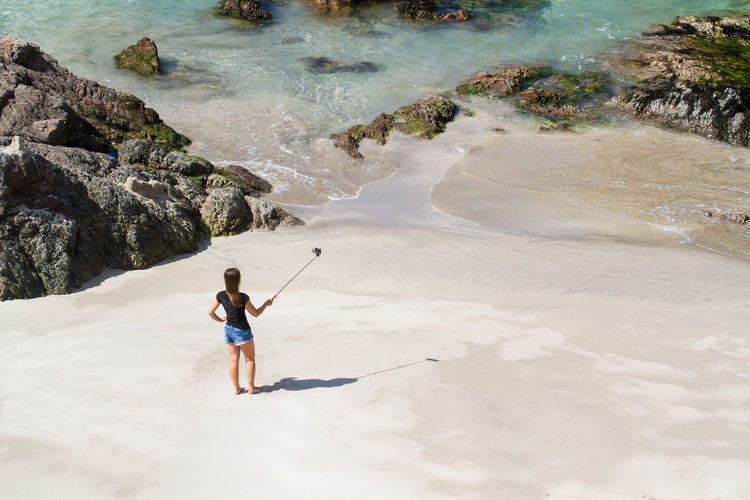 A young girl in shorts and t shirt on a white sandy beach and taking a selfie on her mobile phone which is attached to a selfie stick. Beach Beachphotography Beach Photography Beach Life Selfies Selfie ✌ Selfie Stick Girl Fashionable Lifestyles Summer Vacations Vacation Holiday Deserted Beach Seaside Ocean Ocean View Young Girl Alone One Person Looking Down Cliffs Woman Selfie✌ Lost In The Landscape
