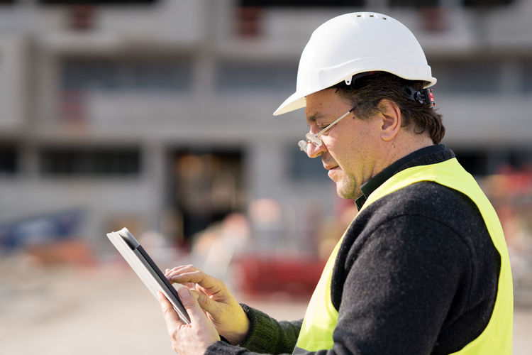 Worker using phone at construction site