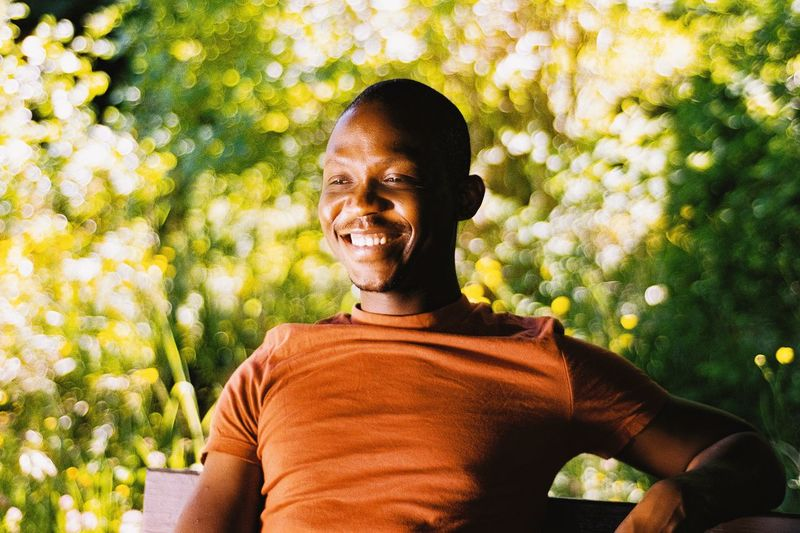Portrait of smiling man from ghana against plants