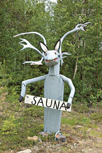 A Reindeer A Reindeer Sculpture A Sauna Advertisement A Wooden Reindeer In Lappland Anthropomorphic By The Roadside Day Folk Art  No People North Finland Outdoors Sculpture Welcome To Sauna