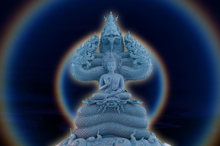Close-up of buddha statue against blue wall