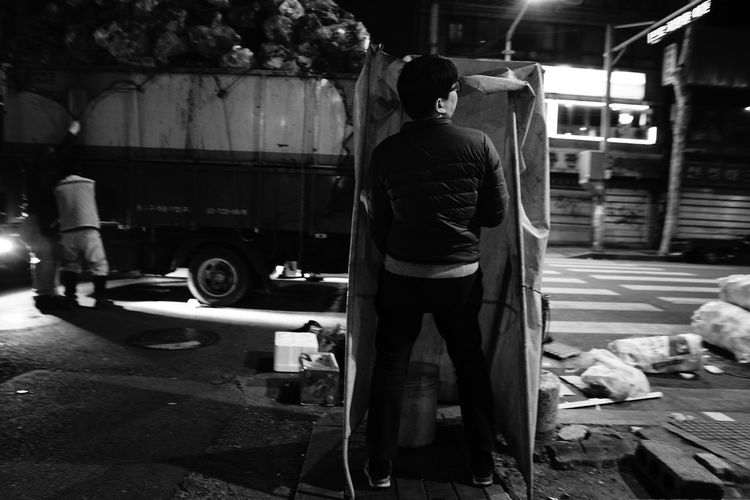 Rear view of man working on street in city at night