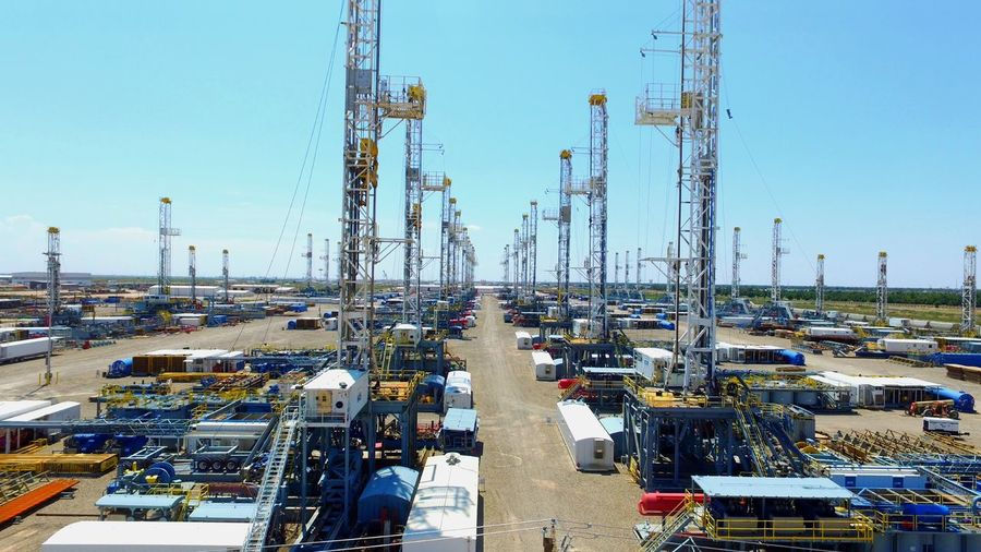 Drilling Rigs On Oil Field Against Sky
