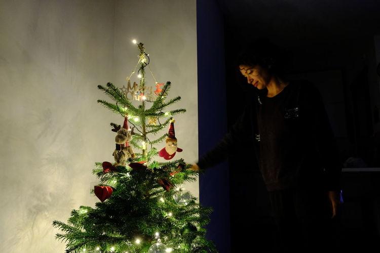 Woman looking at illuminated christmas tree