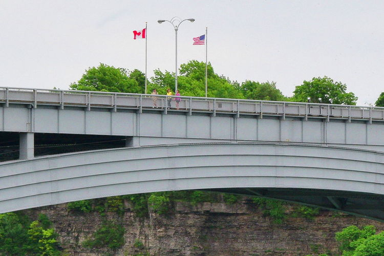 American Flag Architecture Borderline Bridge Building Exterior Built Structure Clear Sky Culture Day Division Flag Flag Pole Fluttering Identity Independence Low Angle View National Flag Patriotism Railing Railings USA Canada Border Wide Wide Shot