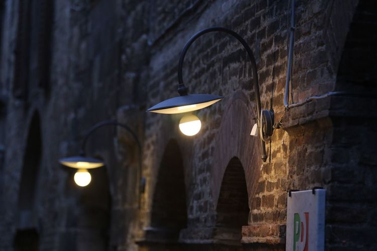 Illuminated electric lights mounted on brick wall of old building